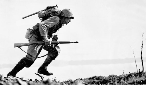 A U.S. Marine charges forward through Japanese machine gun fire on Okinawa. Marines and infantry of the U.S. 10th Army controlled three-quarters of Okinawa three weeks after landing on the island on March 31, 1945.