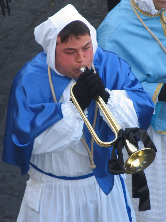 A horn-blower announces the start of the procession, which winds along the island's south coast.