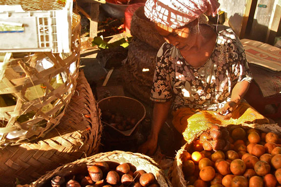 Monsaro, a Balinese salak vendor, waits for customers amidst her fruity fares.
