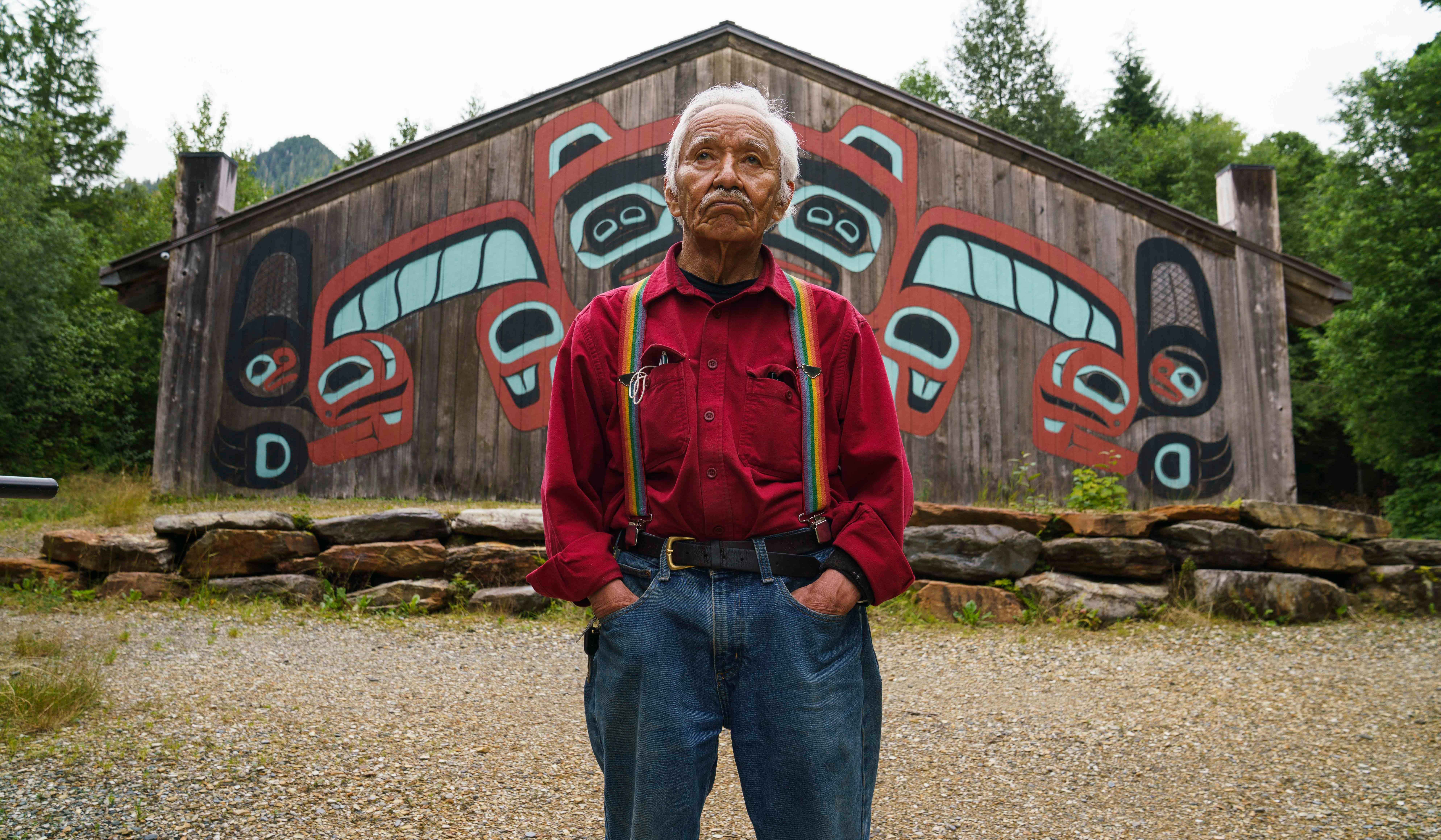 Nathan Jackson, a Chilkoot Sockeye clan leader, in front of a Beaver Clan house screen that adorns a longhouse at Saxman Totem Park. The house screen was carved on vertical cedar planks before it was raised and assembled on the house front. Jackson, who led the project, found his way back to his heritage circuitously after a boyhood spent at a boarding school that prohibited native languages and practices.