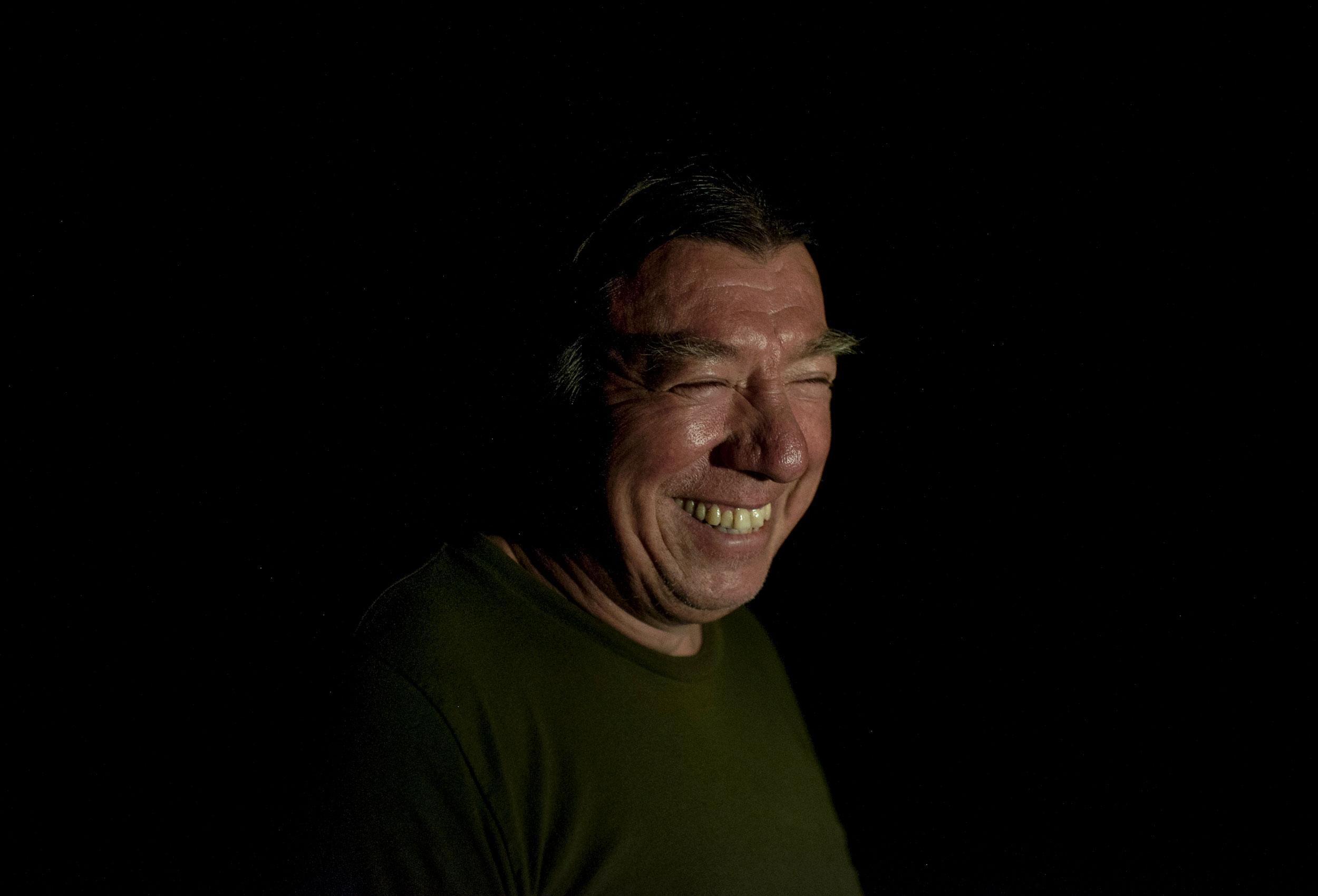 Prosper, smiling in the light of his kerosene lantern