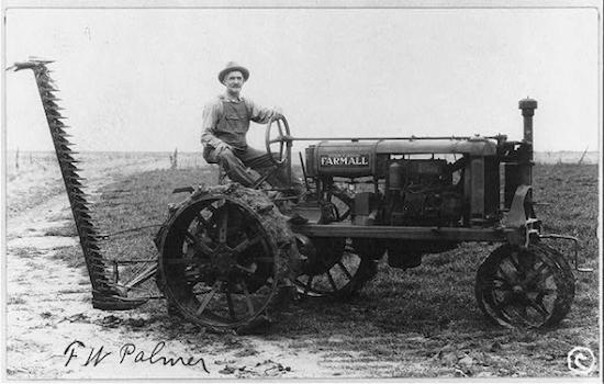 American farmer operating a tractor and reaper