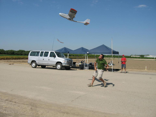 A researcher launches a drone while a backup pilot stands by with radio controls in hand