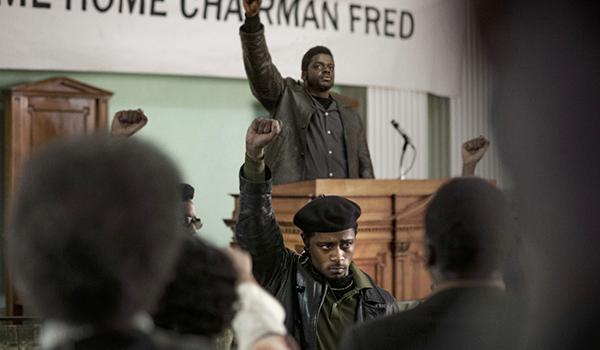 Informer William O'Neal (played by LaKeith Stanfield, seen wearing a beret in the foreground) provided the FBI with information used to plan Black Panther Party Chairman Fred Hampton's assassination (portrayed by Daniel Kaluuya, standing with hand raised at the podium).