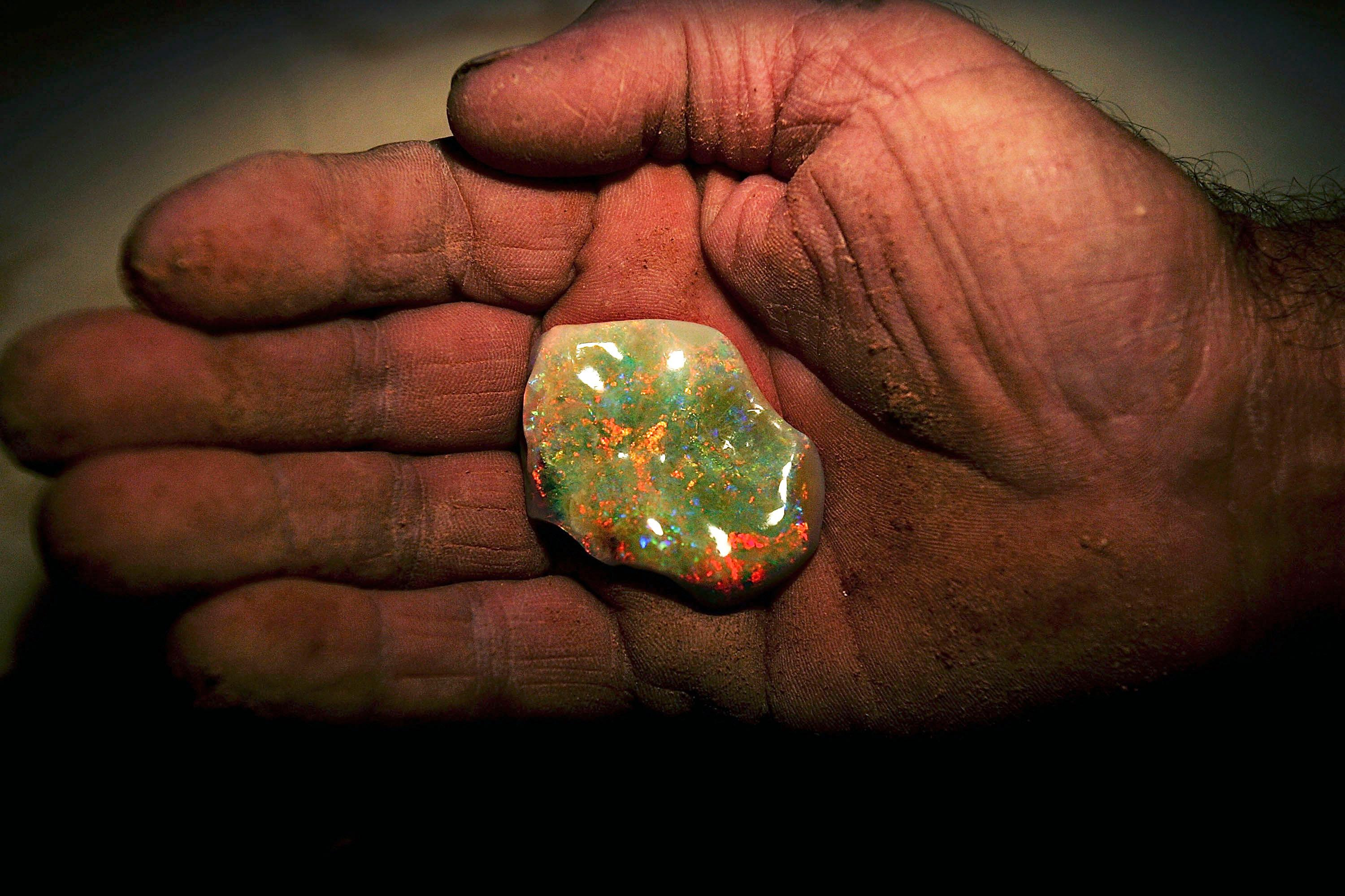 Coober Pedy miner holds a finished opal