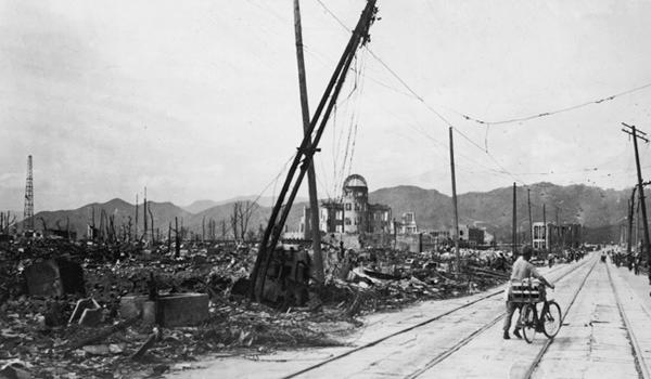 A man wheels his bicycle through Hiroshima days after an atomic bomb leveled the city.