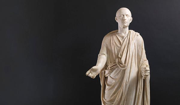 A marble funerary statue of a man wearing a toga, created during the first century A.D.