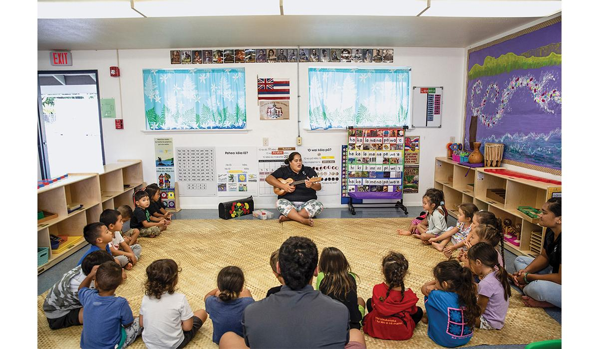 Nāoli Weller, a nursery school teacher at Nāwahī, leads her class in traditional songs. In the room hang signs that help pupils master the Hawaiian language.