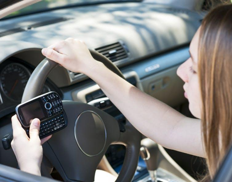 A teenager texts on her cellphone as she drives.