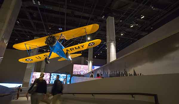 """The """"Spirit of Tuskegee"""" hangs from the ceiling at the Smithsonian's National Museum of African American History and Culture. The blue and yellow Stearman PT 13-D was used to train black pilots from 1944 to 1946."""